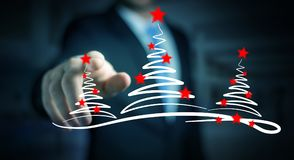 Businessman holding and touching christmas trees sketch. Businessman on blurred background holding and touching christmas trees sketch Stock Images