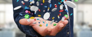 Businessman holding and touching floating medicine pills 3D rend Stock Photo
