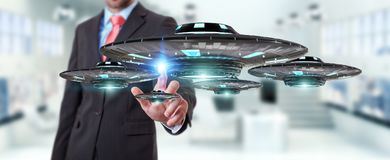 Businessman with retro UFO spaceship 3D rendering. Businessman on blurred background with retro UFO spaceship 3D rendering Stock Photos