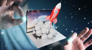 Businessman with rocket launching from a laptop 3D rendering. Businessman on blurred background with rocket launching from a laptop 3D rendering Royalty Free Stock Photos