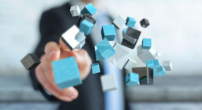Businessman touching floating blue shiny cube network 3D renderi. Businessman on blurred background touching floating blue shiny cube network 3D rendering Royalty Free Stock Photography