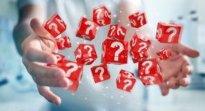 Businessman using cubes with 3D rendering question marks. Businessman on blurred background using cubes with 3D rendering question marks Royalty Free Stock Images