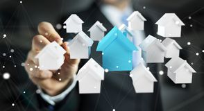 Businessman using 3D rendered small white and blue houses. Businessman on blurred background using 3D rendered small white and blue houses Royalty Free Stock Photos