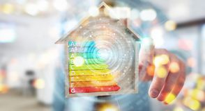Businessman using 3D rendering energy rating chart in a wooden h. Businessman on blurred background using 3D rendering energy rating chart in a wooden house Stock Images