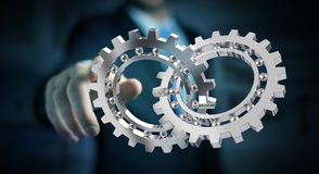 Businessman using floating modern gear mechanism 3D rendering. Businessman on blurred background using floating gear icons 3D rendering Stock Image