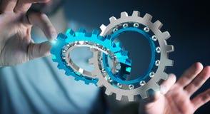 Businessman using floating modern gear mechanism 3D rendering. Businessman on blurred background using floating gear icons 3D rendering Royalty Free Stock Image
