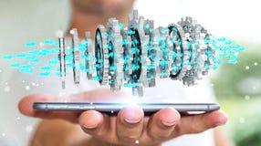 Businessman using floating modern gear mechanism 3D rendering. Businessman on blurred background using floating gear icons over phone 3D rendering Royalty Free Stock Photo