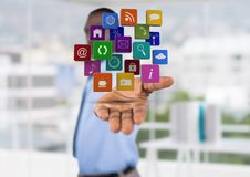 Businessman (blurred) with hand spread of with application icons over. Blurred office background Stock Photos
