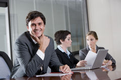 Businessman in boardroom with female colleagues Stock Image
