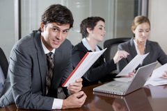 Businessman in boardroom with female colleagues Stock Photo