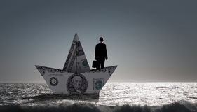 Businessman in boat made of dollar banknote Stock Photography
