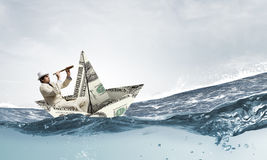 Businessman in boat made of dollar banknote Royalty Free Stock Photo