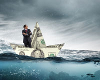 Businessman in boat made of dollar banknote Stock Image