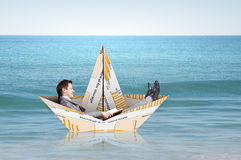 Businessman in boat made of paper Stock Photos