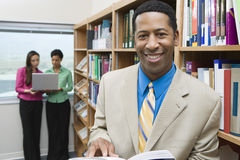 Businessman With Book In Library Royalty Free Stock Photography