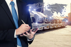 Businessman is booking with blurred cargo , transportation port. And world map. Transportation logistic business concept. Elements of this image furnished by Royalty Free Stock Images