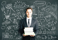 BUsinessman with books and concept strategy scheme on blackboard Royalty Free Stock Image
