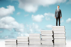 Businessman and books in sky. Businessman standing on book stacks in the sky. 3D Rendering Royalty Free Stock Image