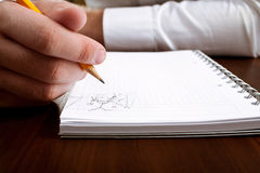 Businessman bored on meeting. Writing sketch in notepad Stock Photo
