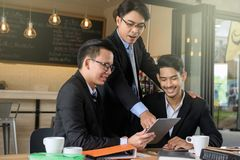 Businessman boss coaching team by tablet. Business men boss coaching two happy young businessman by using digital tablet to show project plan and update progress Royalty Free Stock Photos