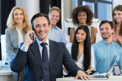 Businessman Boss Talking On Mobile Phone Call Over Mix Race Business People Group Standing Behind At Modern Office stock photo