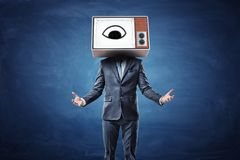A businessman with both arms in front of him palms up and a head replaces by a TV box with an eye on the screen. Royalty Free Stock Image