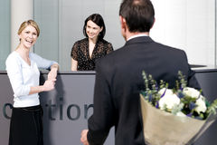 Businessman with bouquet of flowers being greeted by two women at office reception royalty free stock photos