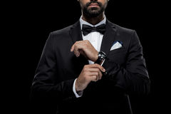 Businessman in bow tie and tuxedo with watch, isolated on black Royalty Free Stock Images
