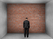 Businessman with bowed head stands front of a brick wall in interior. Royalty Free Stock Photography