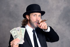 Businessman with bowler hat in black suit showing money and smok Stock Photography
