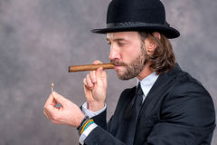Businessman with bowler hat in black suit smoking big cigar Stock Photography