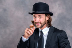 Businessman with bowler hat in black suit smoking big cigar Stock Images