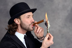 Businessman with bowler hat lighting big cigar with money Stock Photography