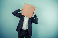 Businessman with box on head has a headache Royalty Free Stock Images