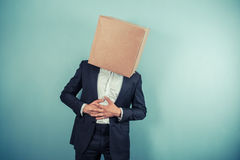 Businessman with box on head has stomach pains. A businessman with a cardboard box on his head is having stomach pains Stock Photo