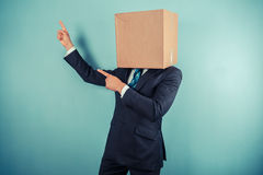 Businessman with box on head is pointing Stock Images