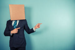 Businessman with box on head is pointing Stock Photos