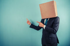 Businessman with box on head is pointing Royalty Free Stock Photo