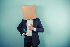 Businessman with box on his head giving thumb up Stock Photography
