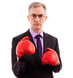 Businessman boxing. Adult angry businessman in boxing gloves Stock Photo