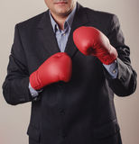 Man in black suit with red boxing gloves royalty free stock photos