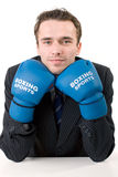 Businessman in boxing gloves isolated. Handsome young man in suit and gloves sitting in office, made in studio isolated on white background Stock Photo