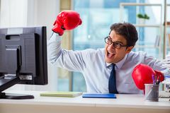 The businessman with boxing gloves in the office Stock Photography