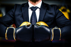 Businessman with boxing gloves is ready for corporate battle. Royalty Free Stock Images