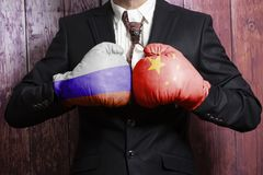 Businessman in boxing gloves with Russian and China flag. Russia versus China concept. On wooden background stock images