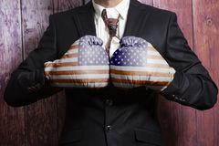 Businessman in boxing gloves with USA flag. On wooden background stock photo