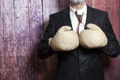 Businessman in boxing gloves. On wooden background royalty free stock photos