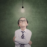 Businessman boy looking at lit bulb Stock Image