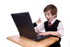 Businessman boy shocked. Young boy dressed in suit looks surprised at his laptop Stock Images
