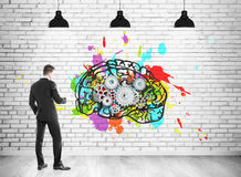 Businessman and brain with cogs. Rear view of a businessman wearing a black suit and looking at a colorful brain sketch with cogs drawn on a white brick wall Royalty Free Stock Photo